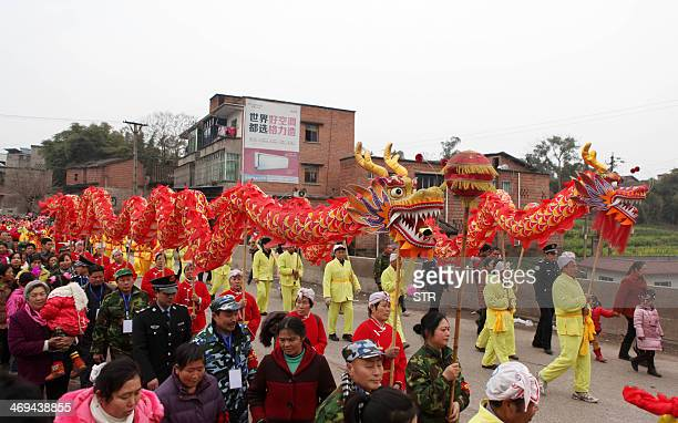 This picture taken on February 14 2014 shows Chinese villagers parade a long dragon to kick off the lantern festival celebration in Yongchuan...