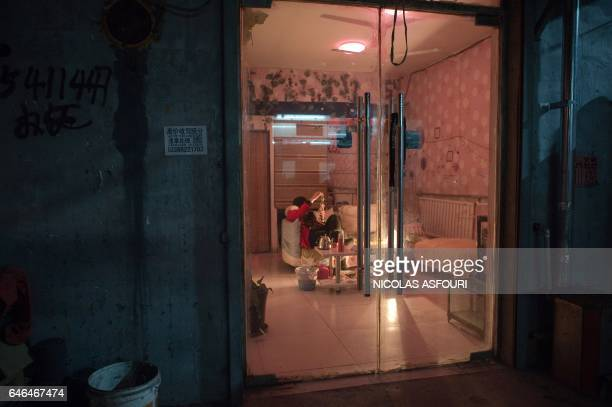 This picture taken on February 15 2017 shows a woman waiting for customers at a massage parlour in the Heiqiaocun migrant village in Beijing China's...