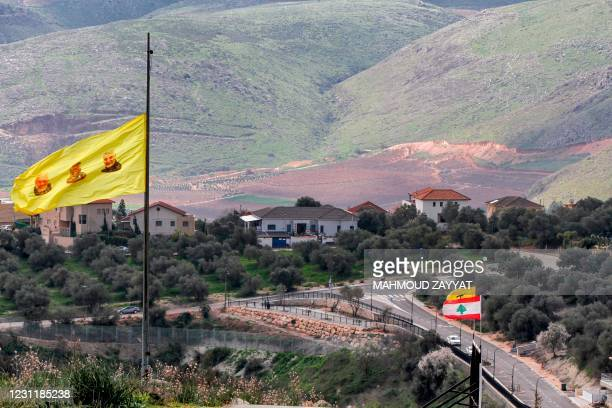 This picture taken on February 15, 2021 shows a banner of Lebanese Shiite movement Hezbollah, showing the faces of slain Iraqi commander of the Iraqi...