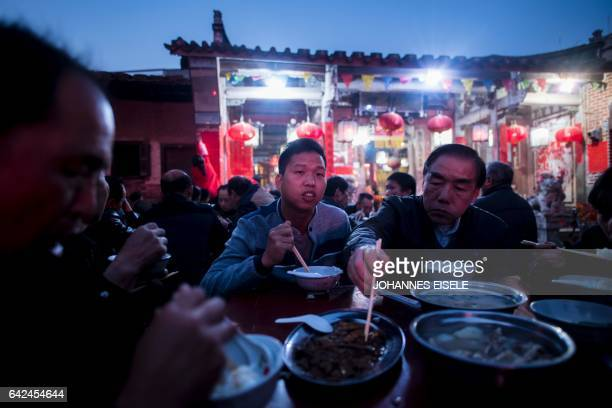 This picture taken on February 16 2017 in Fangshan village in China's coastal province Fujians shows Zheng Yinquan having dinner in front of the...