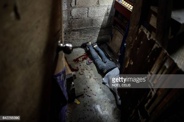 This picture taken on February 16 2017 shows the dead body of a suspected drug dealer on the ground inside a house after unidentified assailants...