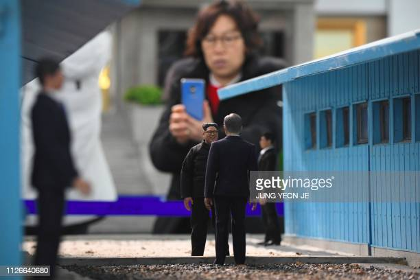 This picture taken on February 16 2019 shows a visitor looking at a miniature set made with figurines showcasing a scene from the first summit...