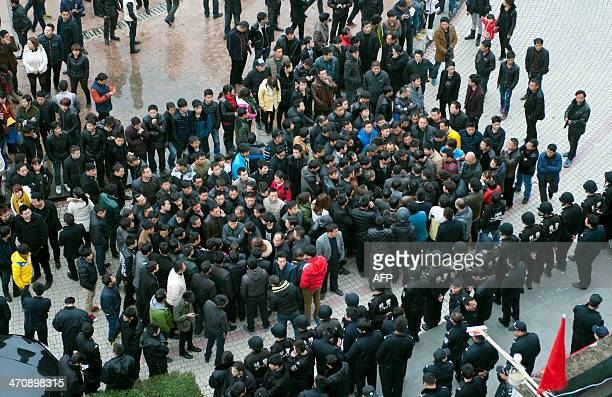This picture taken on February 17 2014 shows workers gathering on a square before the government headquaters in Wenling east China's Zhejiang...