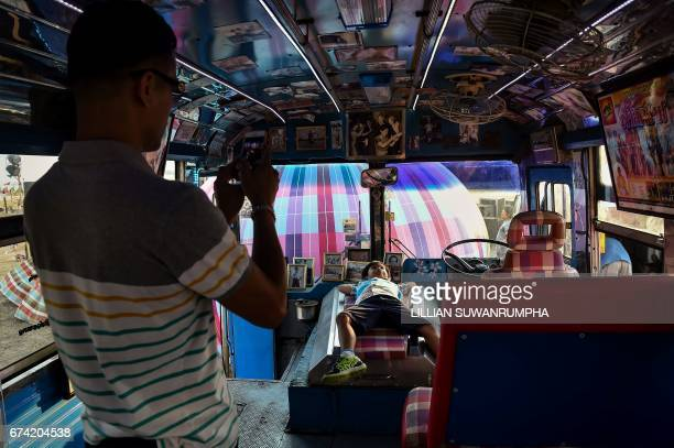 This picture taken on February 17 2017 shows a boy having his picture taken inside the Molam Bus at the Wonderfruit music festival in Chonburi...