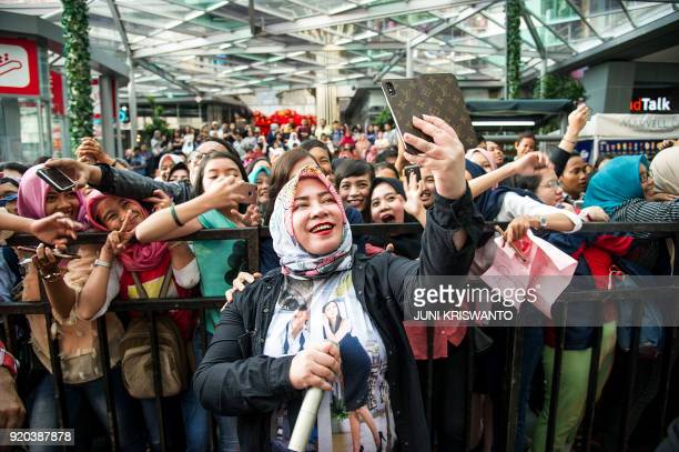 This picture taken on February 18 2018 shows Indonesian singer Meliana Cessy Goeslaw posing for a selfie with fans during a promotional event in...