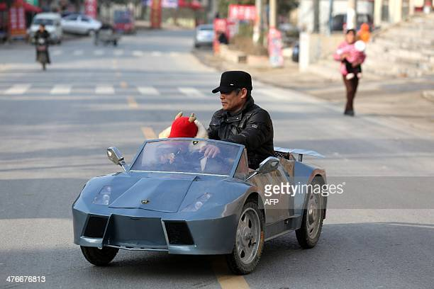 This picture taken on February 19 2014 shows Guo a farmer in his 50s sits in his selfmade scale replica of a Lamborghini with his grandson in a...