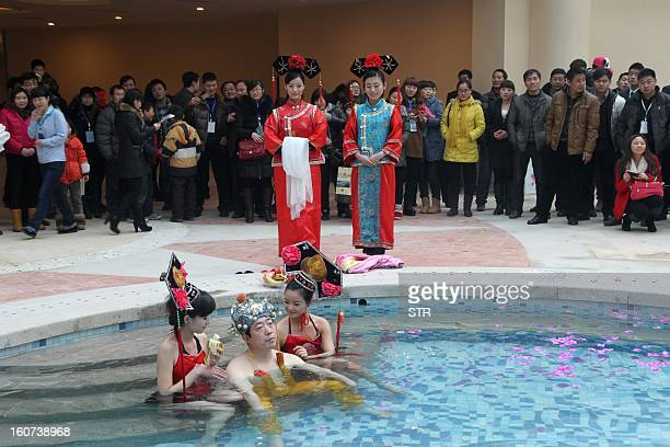 This picture taken on February 2 2013 shows a man sitting between two attendants dressed in costume feeding him bananas as onlookers watch at a...