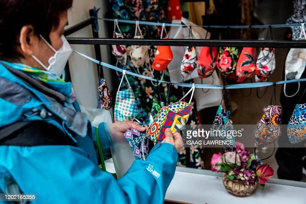 This picture taken on February 20, 2020 shows a customer browsing through protective masks made out of patterned material for sale at a shop in Hong...