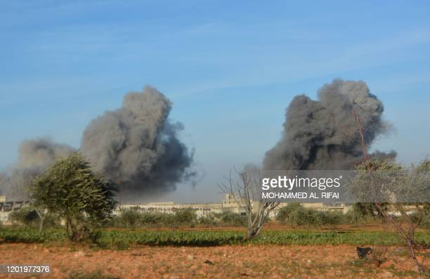 This picture taken on February 20 2020 shows smoke plumes rising following an air strike by progovernment forces on the western sector of the...