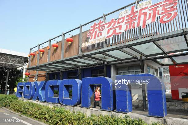 This picture taken on February 22 2013 shows a young woman walking past a Foxconn recruitment point in Shenzhen south China's Guangdong province...