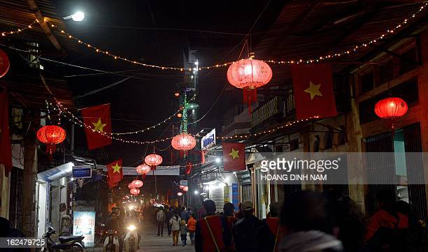 This picture taken on February 22 2013 shows villagers and visitors walking under Chinesemade red lanterns hanging in the village of Uoc Le on the...