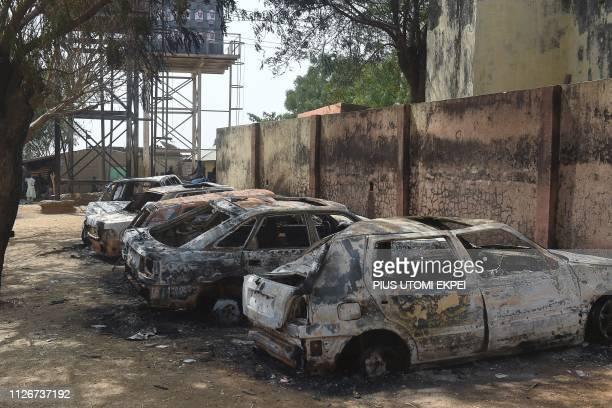 This picture taken on February 22 2019 shows burnt cars following deadly clashes between supporters of the ruling All Progressives Congress and the...