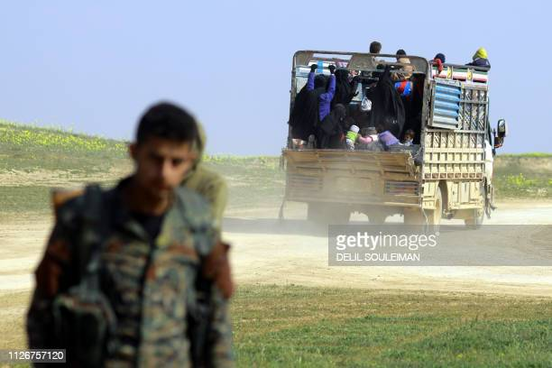 This picture taken on February 22 2019 shows fighters with the USbacked Syrian Democratic Forces near a truck carrying people fleeing the Islamic...