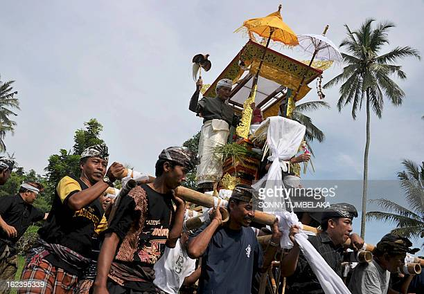 This picture taken on February 22 shows Balinese people carrying a ''bade'', or cremation tower during a procession for a cremation ceremony, known...