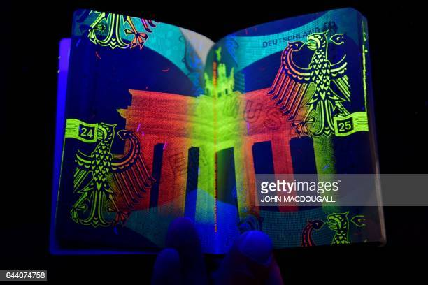 This picture taken on February 23 2017 in Berlin shows a new German electronic passport under ultraviolet light revealing the security hologram prior...