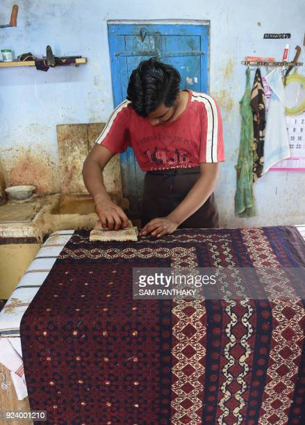 This picture taken on February 23 2018 shows an Indian artisan making traditional Ajrakh block printing designs on bedsheets at a workshop at Khavda...