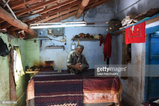 This picture taken on February 23 2018 shows Indian artisan Indris Haji Khatri making traditional Ajrakh block printing designs on bedsheets at a...