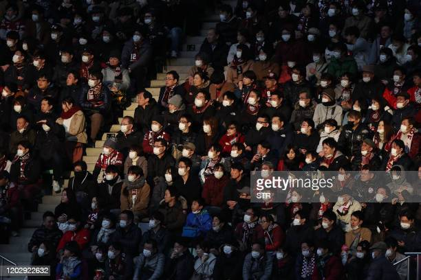 TOPSHOT This picture taken on February 23 2020 shows audience members wearing face masks at a JLeague football match between Vissel Kobe and Yokohama...