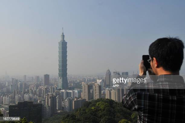 This picture taken on February 25 2013 shows a tourist taking photos of Tower 101 as a haze of pollution sits over the city's skyline on a clear day...