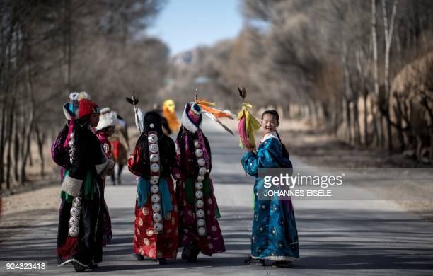 TOPSHOT This picture taken on February 25 2018 shows girls dressed in traditional Tibetan costumes walking down a road after a festival to mark the...