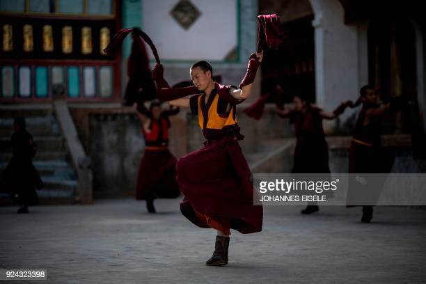 This picture taken on February 25 2018 shows monks practicing a Cham dance in front of a temple to prepare for a festival during the Tibetan New Year...