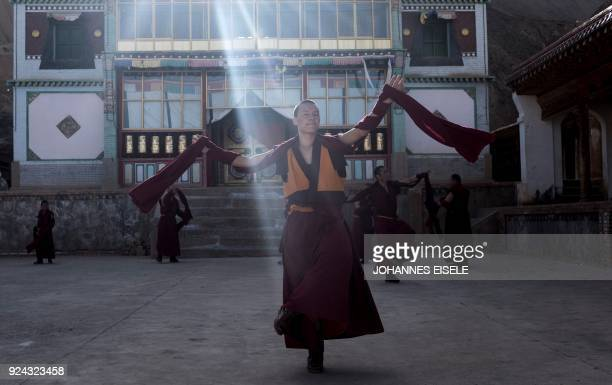 TOPSHOT This picture taken on February 25 2018 shows monks practicing a Cham dance in front of a temple to prepare for a festival during the Tibetan...