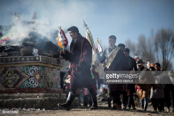 This picture taken on February 25 2018 shows villagers burning incense near a temple during a festival to mark the Tibetan New Year celebrations in...