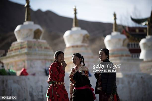 This picture taken on February 25 2018 shows young women dressed in traditional Tibetan clothing standing in front of a monastery during a festival...