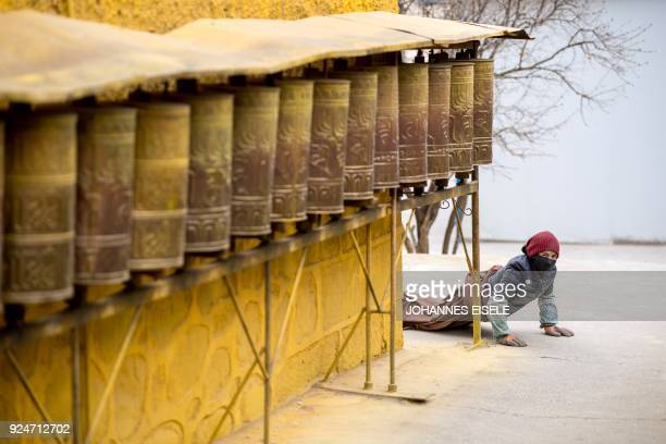 This picture taken on February 26 2018 shows a Tibetan devotee prostrating at the Longwu Temple during Tibetan New Year celebrations in Tongren on...