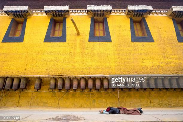 TOPSHOT This picture taken on February 26 2018 shows a Tibetan devotee prostrating at the Longwu Temple during Tibetan New Year celebrations in...