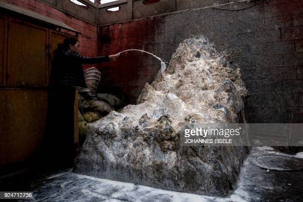 This picture taken on February 26 2018 shows a Tibetan devotee splashing milk as an offering at the Longwu Temple during Tibetan New Year...