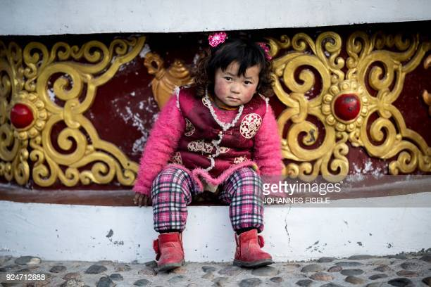 This picture taken on February 26 2018 shows a Tibetan girl attending a local festival to mark the Tibetan New Year celebrations in the village of...