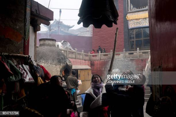 This picture taken on February 26 2018 shows a Tibetan woman helping a child to ring a bell at the Longwu Temple during Tibetan New Year celebrations...