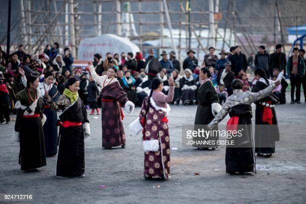 This picture taken on February 26 2018 shows Tibetan women dancing during a local festival to mark the Tibetan New Year celebrations in the village...