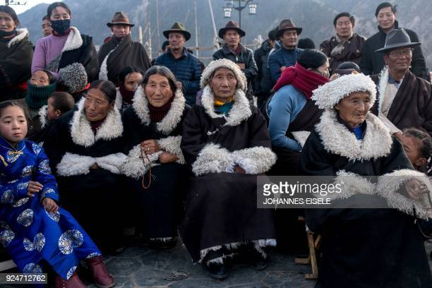 This picture taken on February 26 2018 shows Tibetan women following a local festival to mark the Tibetan New Year celebrations in the village of...