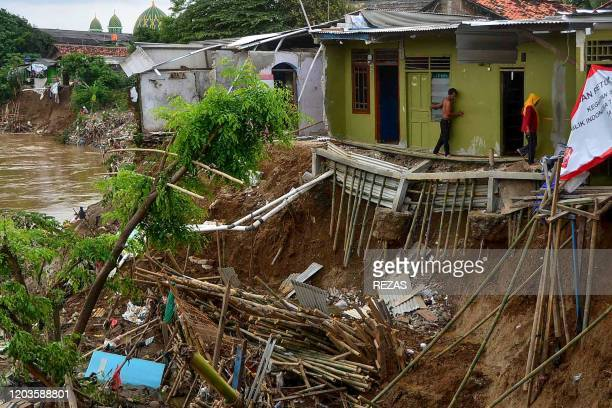 TOPSHOT This picture taken on February 26 2020 shows residents walking precariously along a makeshift bamboo walkway between a house and flooderoded...