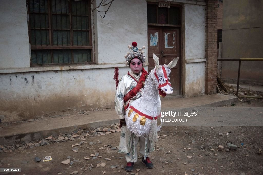 This picture taken on February 27, 2018 shows a boy dressed in traditional costume posing for a photo before he attends the She Huo festival in Longxian, Shaanxi province. Villagers in northern China wake up before dawn to paint their faces with pinkish make-up, don colourful robes and wield swords to represent legendary figures for the She Huo festival, a unique event capping Chinese New Year celebrations. / AFP PHOTO / Fred DUFOUR
