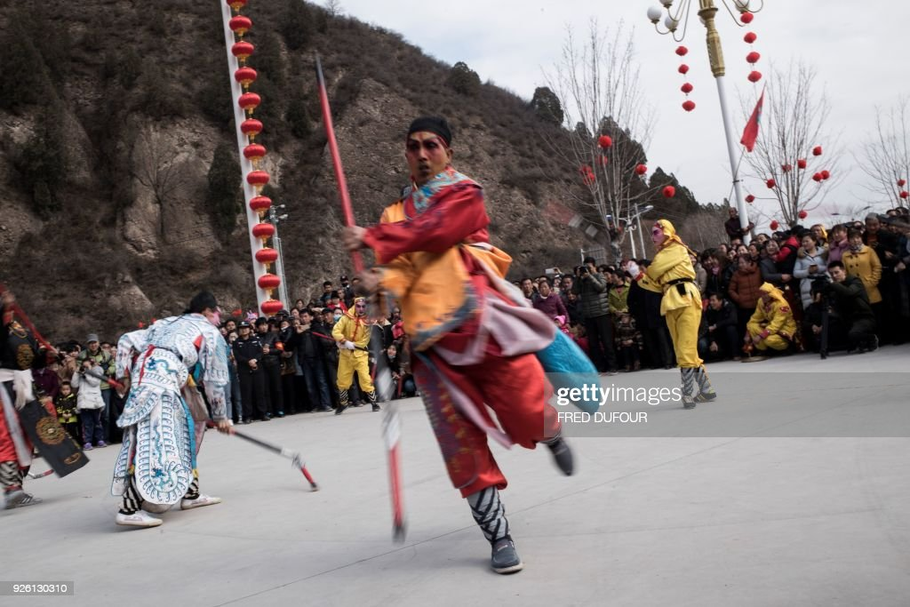 This picture taken on February 27, 2018 shows villagers dressed in traditional costume as they parade during the She Huo festival in Longxian, Shaanxi province. Villagers in northern China wake up before dawn to paint their faces with pinkish make-up, don colourful robes and wield swords to represent legendary figures for the She Huo festival, a unique event capping Chinese New Year celebrations. / AFP PHOTO / Fred DUFOUR