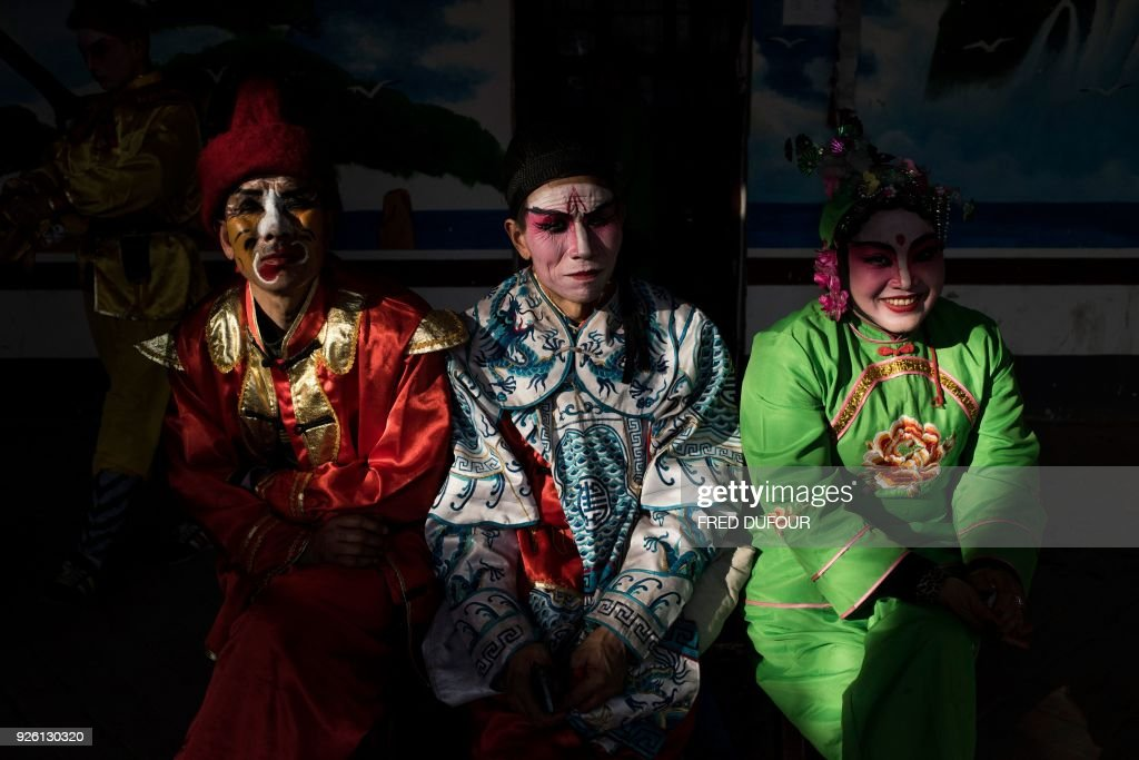 This picture taken on February 27, 2018 shows villagers dressed in traditional costume taking a rest as they attend the She Huo festival in Longxian, Shaanxi province. Villagers in northern China wake up before dawn to paint their faces with pinkish make-up, don colourful robes and wield swords to represent legendary figures for the She Huo festival, a unique event capping Chinese New Year celebrations. / AFP PHOTO / Fred DUFOUR