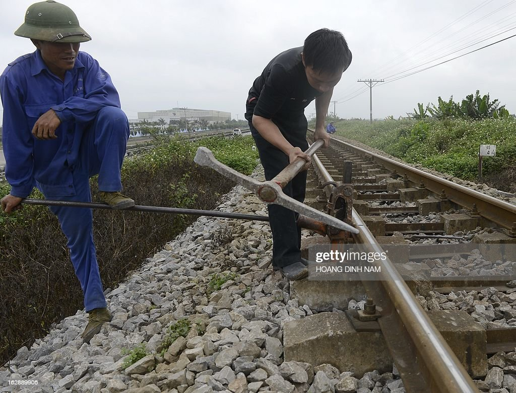 This picture taken on February 28, 2013 shows workers from a railway maintenance service working on a portion of a railway in northern province of Hai Duong. Vietnam's railway network, whose status is described by some official published reports as remaining the same one as hundred years ago when it was first built in French colonial time, is subjected to a national upgrading program approved by the central government. AFP PHOTO/HOANG DINH Nam