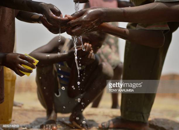 This picture taken on February 28 2015 shows a children drink from a contaminated borehole at Rier village in south Sudan's Unity state near an...