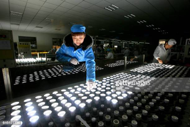 This picture taken on February 28 2017 shows Chinese employees working on an energysaving bulb production line at a lighting factory in Suining...