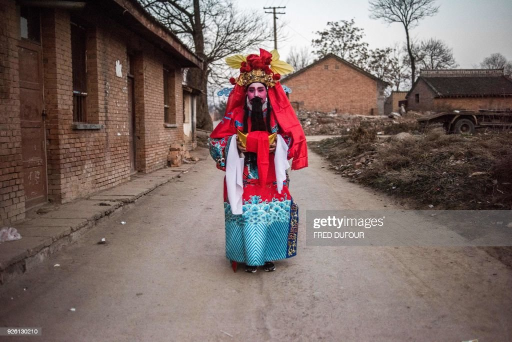 This picture taken on February 28, 2018 shows a villager dressed in traditional costume posing before he parades during the She Huo festival on the outskirts of Longxian, Shaanxi province. Villagers in northern China wake up before dawn to paint their faces with pinkish make-up, don colourful robes and wield swords to represent legendary figures for the She Huo festival, a unique event capping Chinese New Year celebrations. / AFP PHOTO / Fred DUFOUR