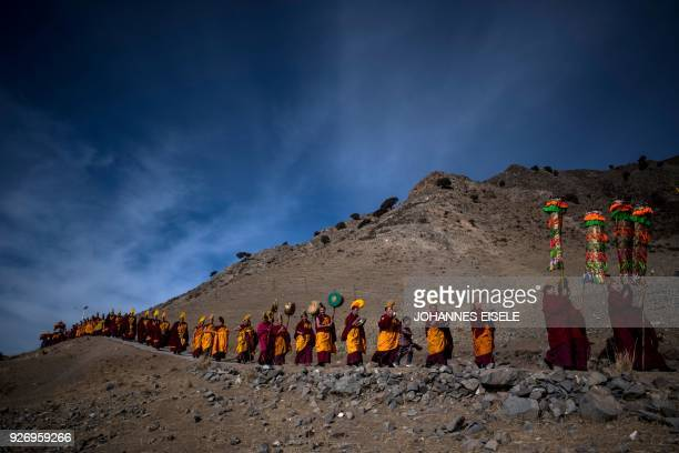 This picture taken on February 28 2018 shows Tibetan Buddhist monks walking to unveil a thangka painting for Monlam otherwise known as the Great...