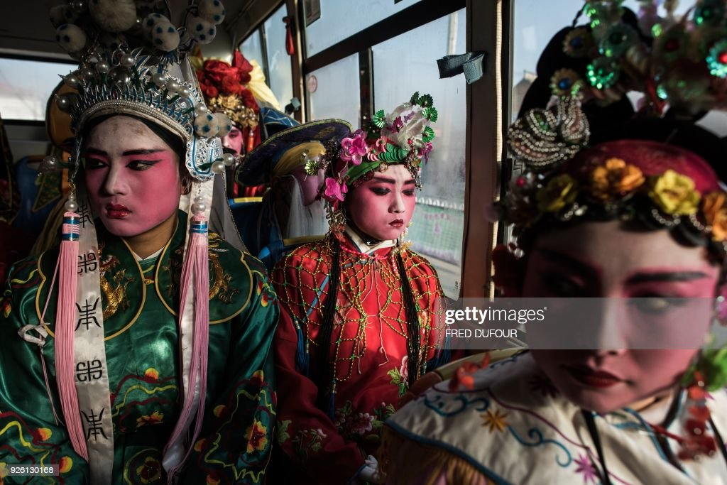 This picture taken on February 28, 2018 shows villagers dressed in traditional costume waiting in a bus to attend the She Huo festival in Longxian, Shaanxi province. Villagers in northern China wake up before dawn to paint their faces with pinkish make-up, don colourful robes and wield swords to represent legendary figures for the She Huo festival, a unique event capping Chinese New Year celebrations. / AFP PHOTO / Fred DUFOUR