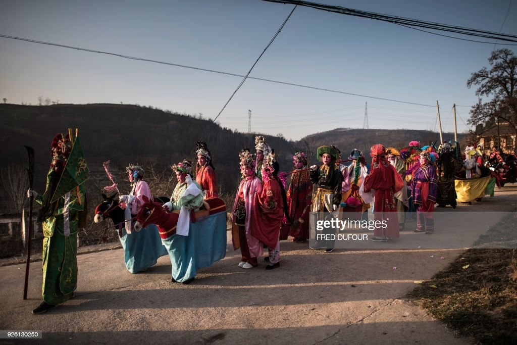 This picture taken on February 28, 2018 shows villagers dressed in traditional costume as they parade during the She Huo festival on the outskirts of Longxian, Shaanxi province. Villagers in northern China wake up before dawn to paint their faces with pinkish make-up, don colourful robes and wield swords to represent legendary figures for the She Huo festival, a unique event capping Chinese New Year celebrations. / AFP PHOTO / Fred DUFOUR
