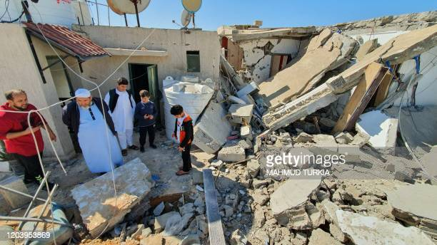 This picture taken on February 28, 2020 shows people inspecting the damage inside a building following a rocket attack by forces loyal to eastern...