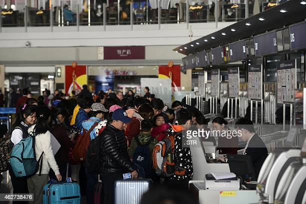 This picture taken on February 3 2015 shows passengers queuing up to check in at the Beijing Capital International Airport in Beijing China's 40day...