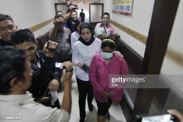 This picture taken on February 3 2020 shows two women arrested for allegedly posting misinformation online relating to the new SARSlike virus that...