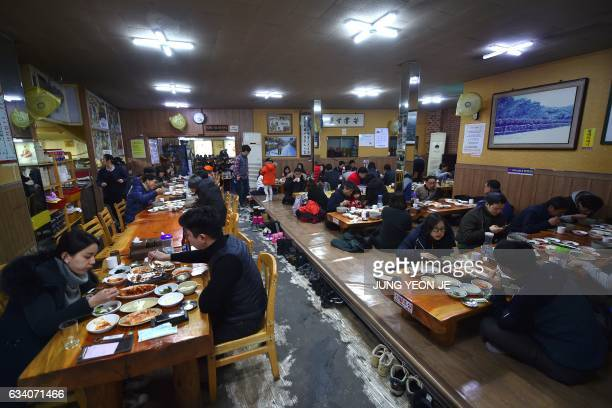 This picture taken on February 4 2017 shows visitors eatting dried pollack hangover soup at a restaurant in Hoenggye town near the venue for the...